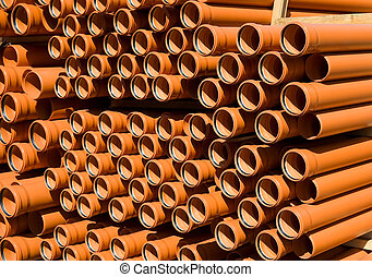 Orange PVC pipes stacked in construction site