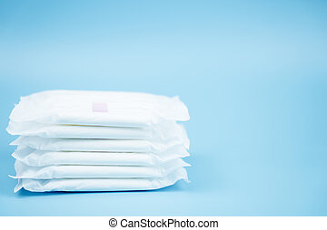 Stacked sanitary napkin pad on blue background.