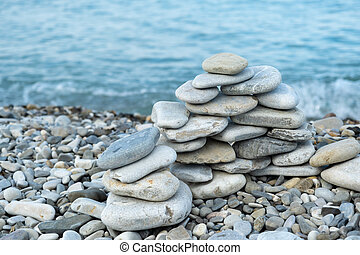 Stacked stone figure on the beach in the morning.