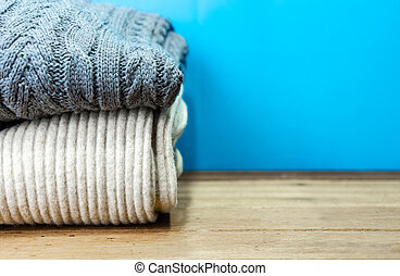 Stacked sweater with copy space on wooden table