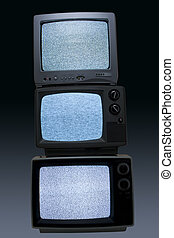 Three old portable tvs stacked displating no channel snow on a gradient background