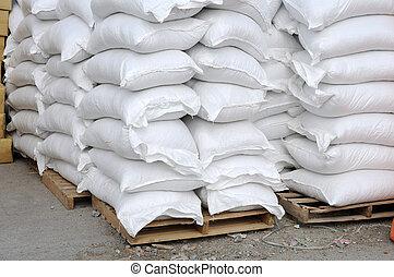 Stacked white sacks at storehouse