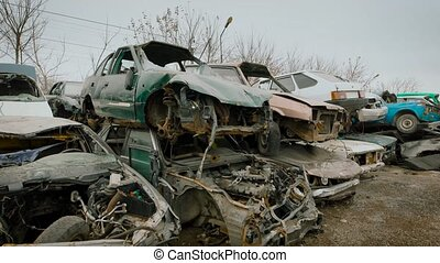 Stacked wrecked cars on grungy junkyard - View of plenty of...