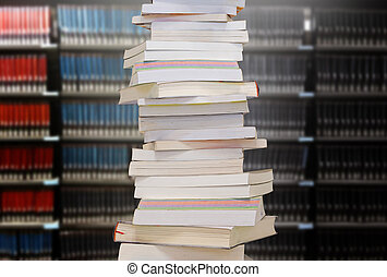 Stacking books with blur bookshelfs background in library room.