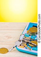 stacking coins and bunch of key on calculator over wooden desk background for home loans concept