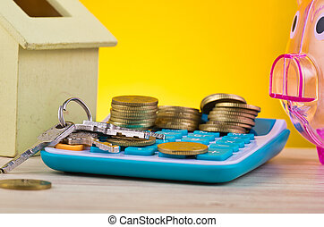 stacking coins and bunch of key on calculator, piggy bank and house replica on wooden desk for home loans concept