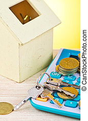 stacking coins and bunch of key on calculator with house replica on wooden desk for home loans concept