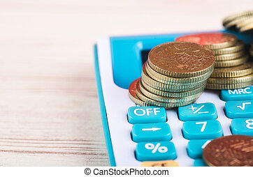 Stacking coins on calculator over wooden background for saving business investment concept