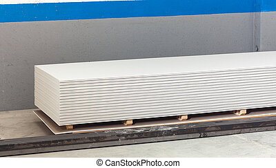 Stacking of white gypsum panels, drywall or plasterboard.