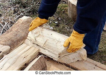 Stacking wood - Woman in jeans and sweatshirt picking up...