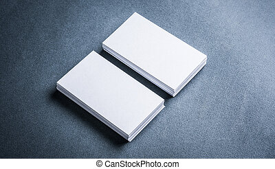 Stacks of blank paper business cards on grey background