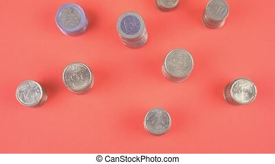 Top view in movement of euro coins on orange background