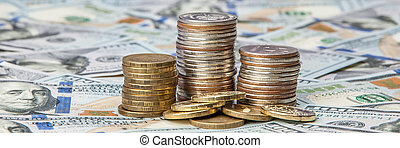 Stacks of coins on the scattered notes of dollars on a brilliant background.