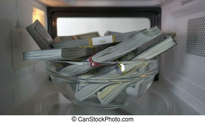 Stacks of dollars hidden in a microwave spinning inside oven