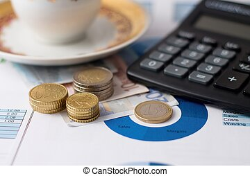 Stacks of euro coins, calculator and coffee cup