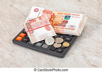 Stacks of five thousandths banknotes of russian roubles, coins and calculator