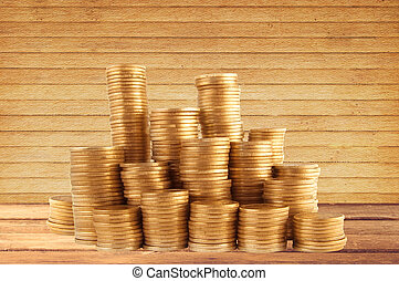 Stacks of golden coins on wooden table background