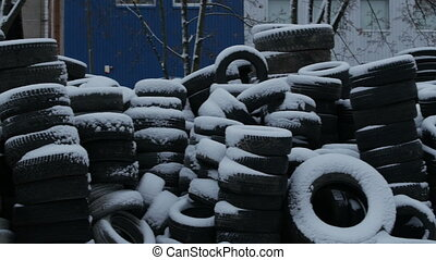 Stacks of tires covered with snow.