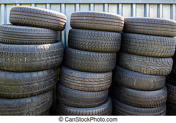 stacks of tires - three stacks of used old tires in front of...