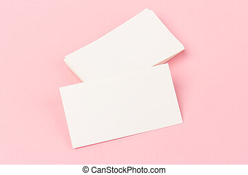 white blank business cards on pink  background in close-up