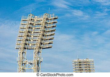 Stadium lights in daytime against blue sky