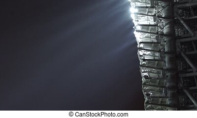 Stadium lights turned on in fog night. Pan