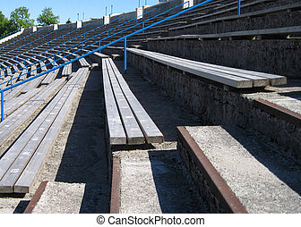 Stadium with a long wooden benches for seats.