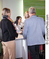 Staff Assisting Senior Passengers At Airport Check-in Desk