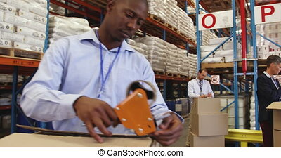 Staff in a warehouse packing boxes for delivery 4k - Close ...