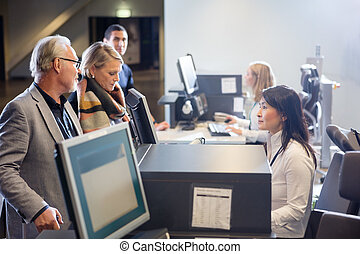 Staff Looking At Senior Business Couple At Airport Check-in Desk