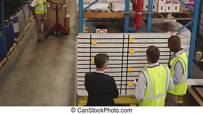 Staff meeting at an information board in a warehouse 4k - ...