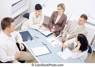 Five business colleagues sitting around table and having a meeting.