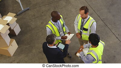 Staff meeting on the warehouse floor 4k - Elevated view of ...