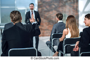 staff member raises a hand at a conference to answer a question