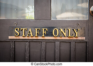 Staff Only Sign on wood door