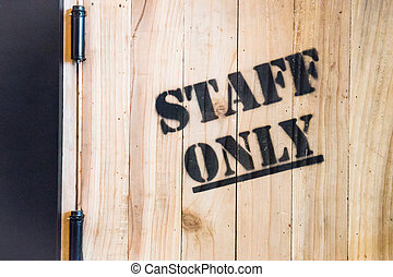 Staff only sign on wooden background