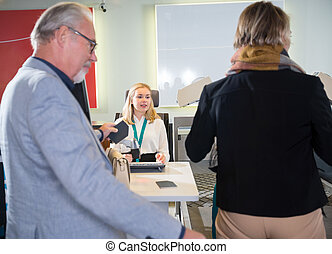 Staff With Senior Passengers At Airport Check-in Desk