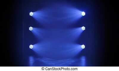 Stage blue floodlights shine during a live show concert, in a night club or party. Dark background. Studio spotlight or projector motion template.