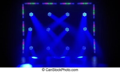 Stage colored floodlights and frame of spotlights shine during a live show concert, in a night club or party. Dark background. Studio spotlight or projector motion template.