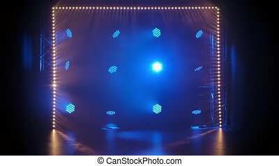 Stage light rays in an empty concert hall. Professional lighting and show effects. Blue dynamic spotlights and spot yellow lighting shine against a black background