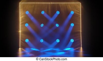 Stage light rays in an empty concert hall. Professional lighting and show effects. Blue spotlights and spot yellow lighting shine against a black background