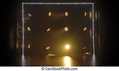 Stage light rays in an empty concert hall. Professional lighting and show effects. Yellow dynamic spotlights and spot white lighting shine against a black background