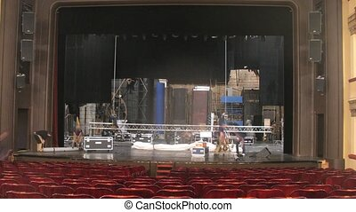 Stagehands dismantle scenery after performance in theatre,...