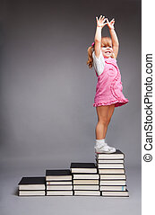Happy little girl standing on the top of the steps books