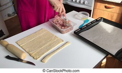 Stages of preparation of meat glomeruli. A woman stirs stuffing. Next to the table is a dough and tools. View from above. Video shot on the iPhone 7 Plus.