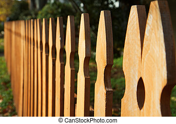 Brown Stain wood fence in perspective with green grass and bushes in background