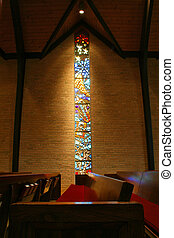 Portrait of a stained glass window inside of a church, with pews in the foreground.