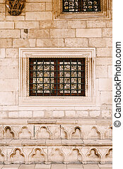 Stained-glass windows with patterns behind a metal lattice on the stone wall of the house.