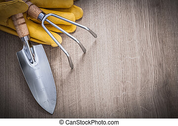 Stainless hand trowel rake yellow leather safety gloves on wood