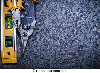Stainless steel cutter gripping tongs construction level on black background.